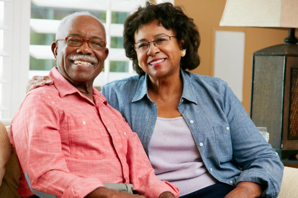older couple sitting on couch together smiling I dentures pikesville MD