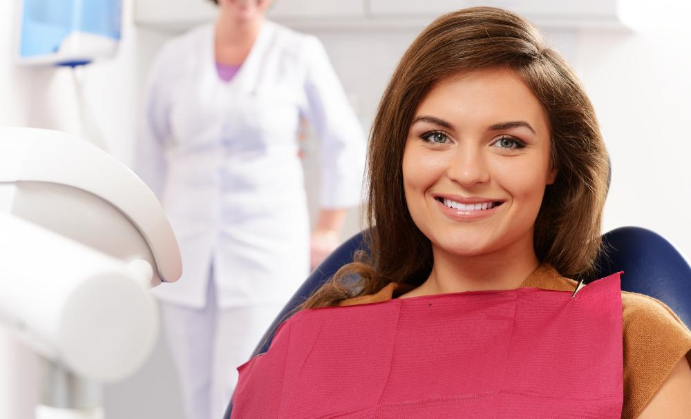 woman sitting in dental exam chair smiling I gum disease treatment pikesville MD
