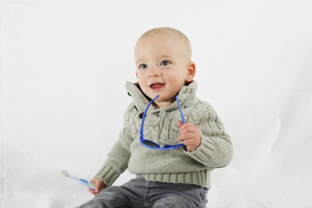 young baby sitting & smiling holding toothbrush I children's dentistry pikesville MD