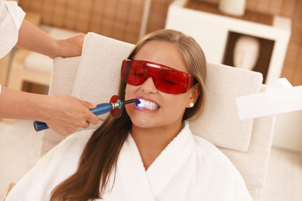 woman sitting in dental exam chair with safety goggles receiving dental filling I dental fillings naylors court dental partners