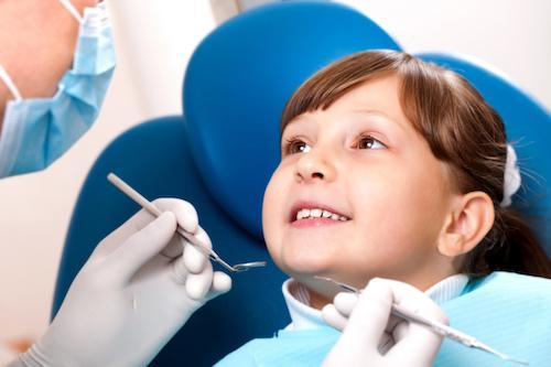Young girl sitting in dental chair smiling l Kids dentist in Pikesville MD
